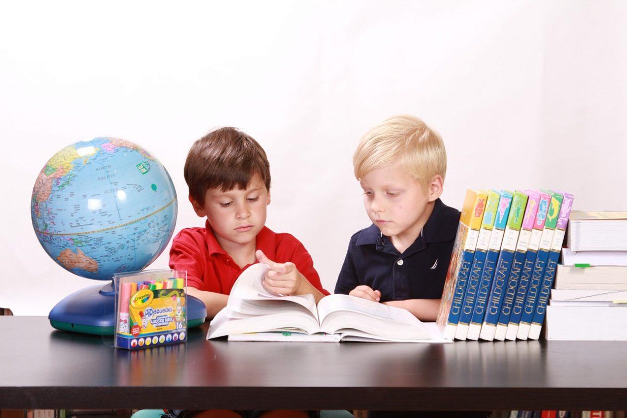 две малки момченца заобградени и учебници и глобус, четат учебник