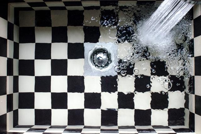 мивка на черно бели квадратчета сифон и течаща вода